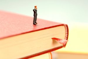 Miniature figurine standing on a book with a bookmark