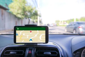 Smart Phone Displaying Map On Dashboard Of Car