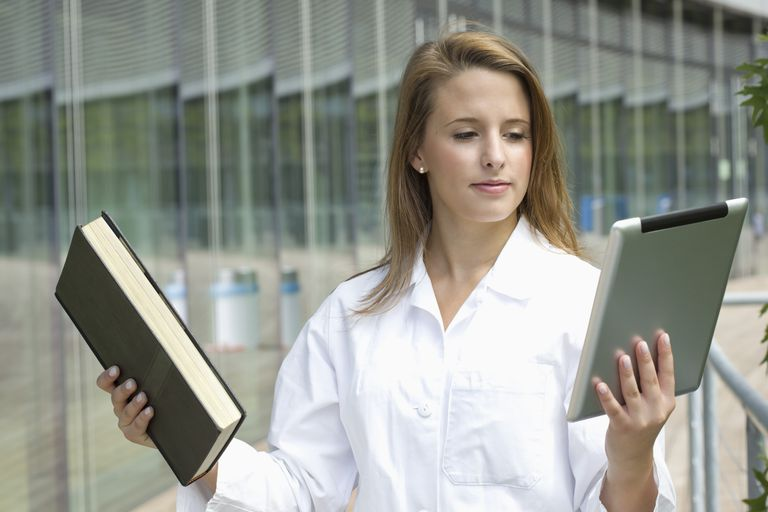 Europe, Germany, North Rhine Westphalia, Duesseldorf, Medical student comparing book with digital tablet