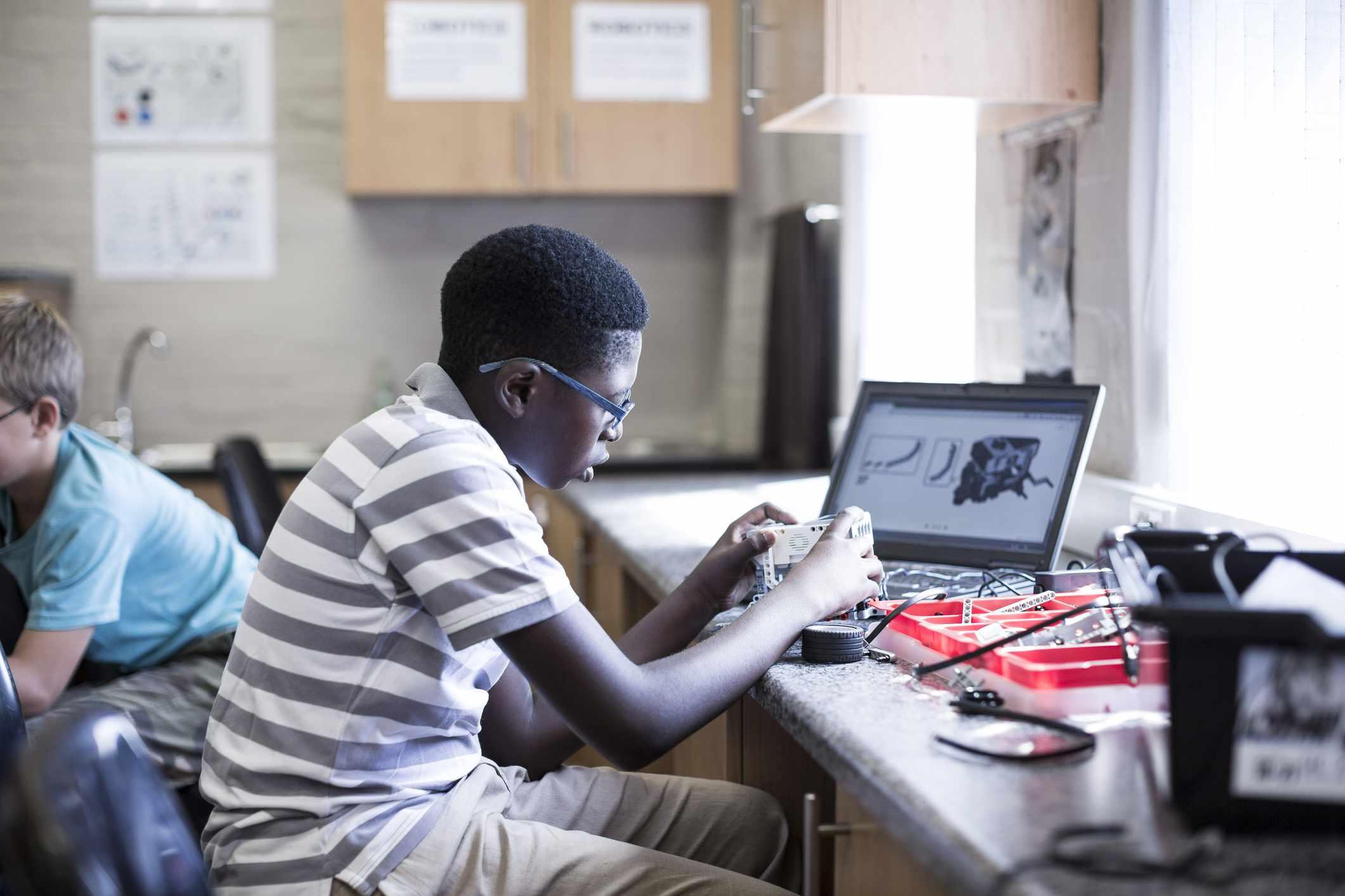 School kids working on robotics design and programming.