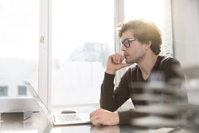 Portrait of young architect using laptop in an office