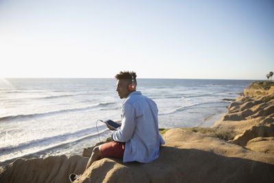 Young African American man with headphones and digital tablet on sunny beach rocks