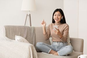 Woman listening to AirPods on the couch