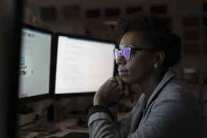 Business woman looking at computer monitors
