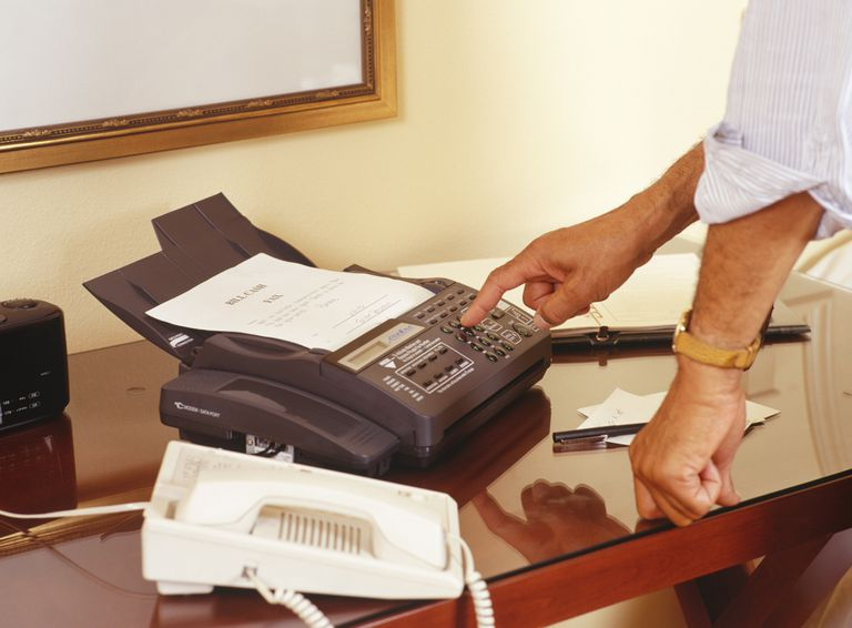 A close-up stock photo of a man using a fax machine that is sitting on a desk.