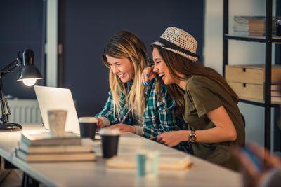 2 women laughing at computer