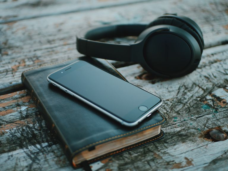iPhone sitting on a book next to a pair of Bluetooth headphones