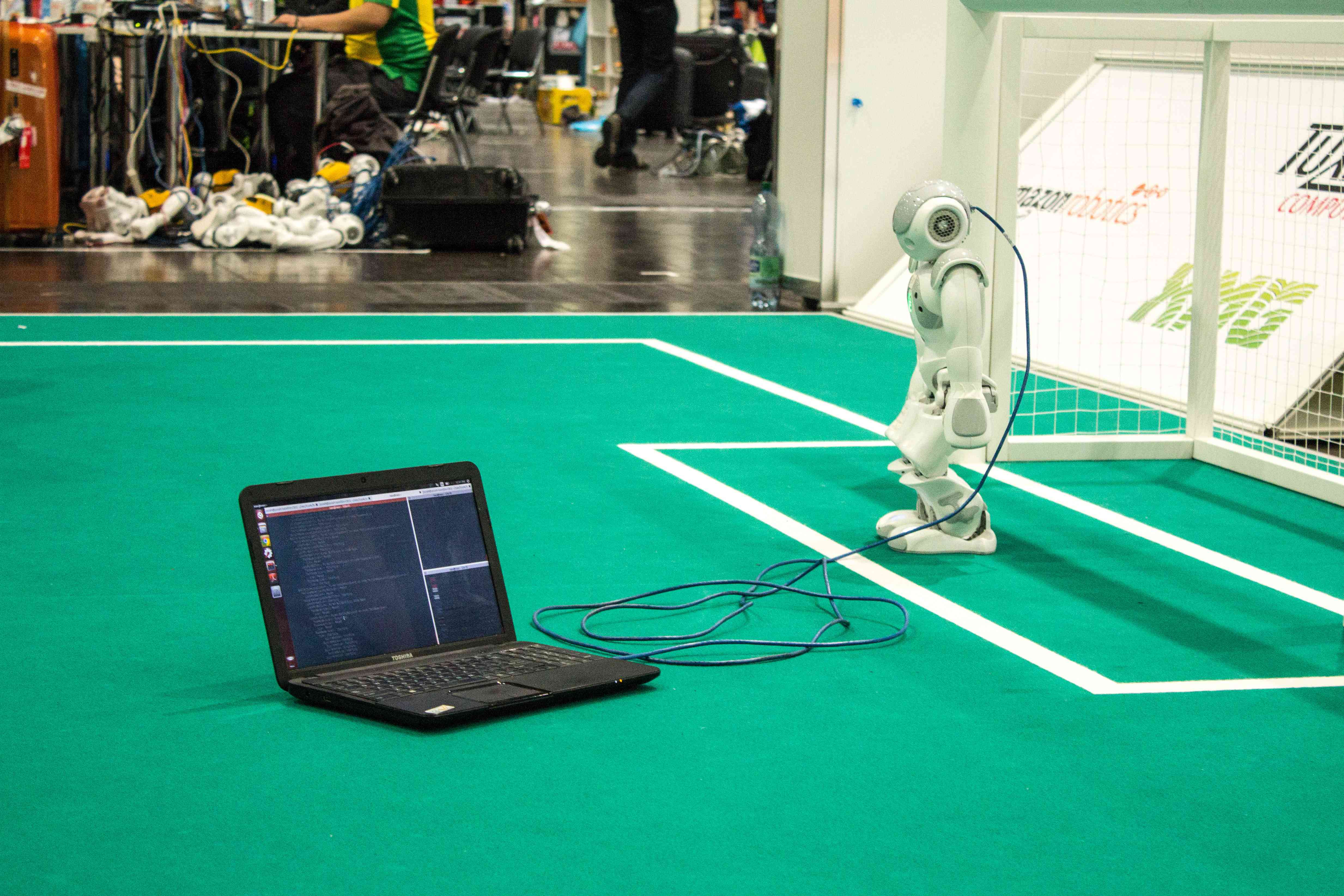 A laoptop computer with code on the screen connected by a wire to a robot.