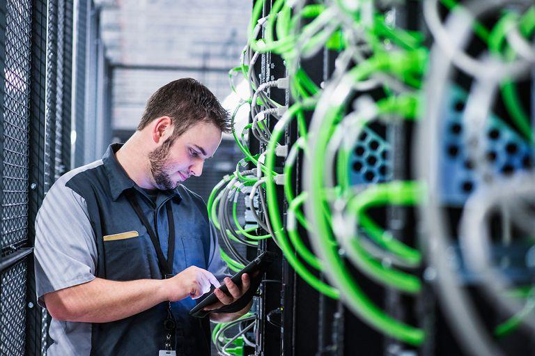 Caucasian technician using digital tablet in server room.