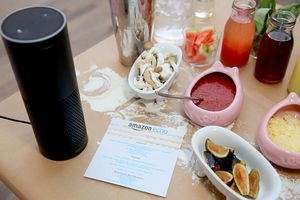 Amazon Echo on table near food from completed meal.