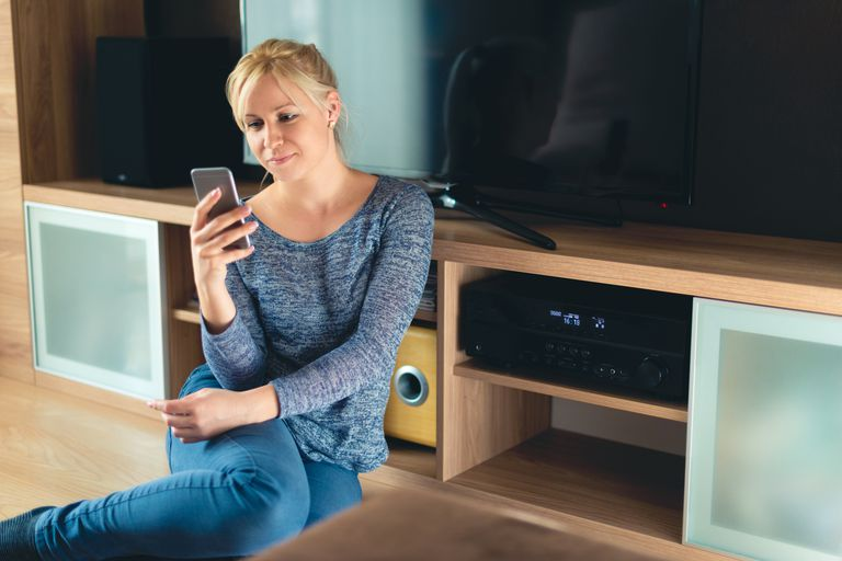 Woman sitting in front of a home theater system holding a smartphone