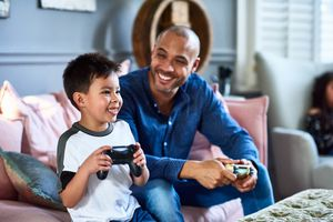 A man and his son are sitting on a cough holding games controllers and smiling together