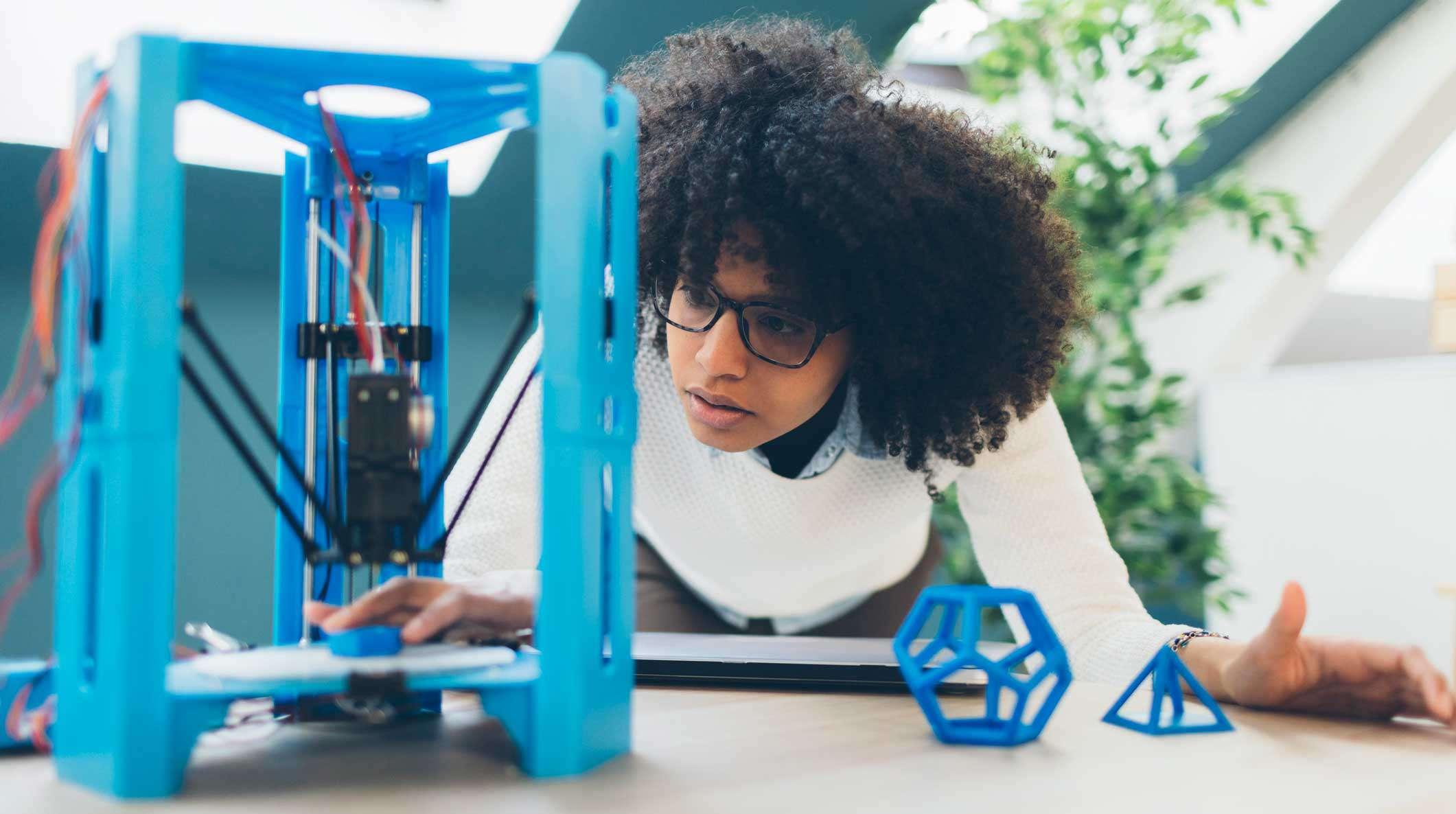Maker watching a 3D printer build a part