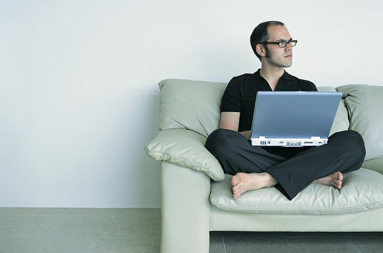 Man looking away sitting cross legged on a sofa using a laptop