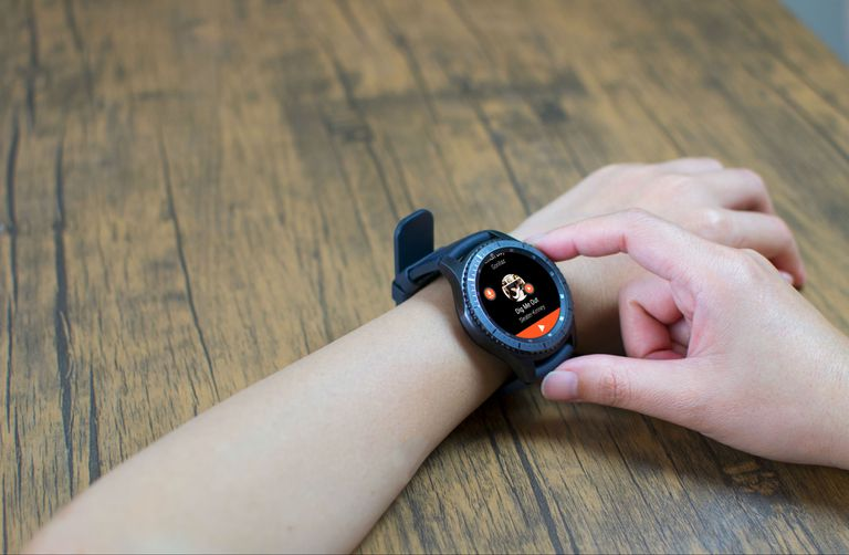 A woman sets her smartwatch with Wear OS 2.0 to download music for offline listening.