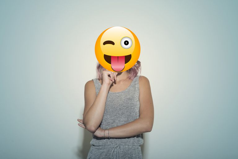 Woman standing in front of a blue wall with an emoji face