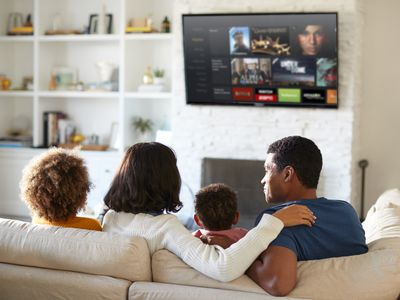 A family sitting on a couch watching HBO Go on a TV via an Amazon Fire Stick.