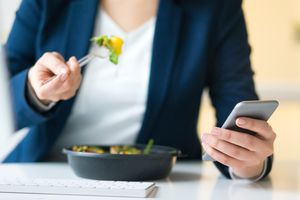 Businesswoman eating a salad and counting its calories with a calorie counter app on her iPhone