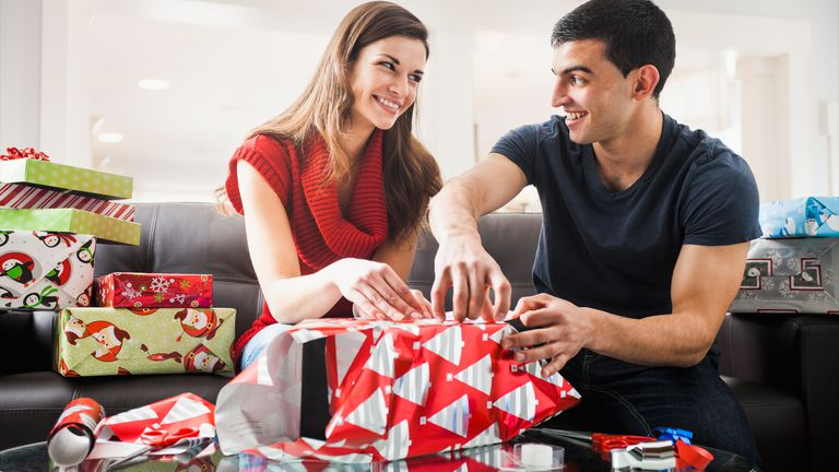 A woman and man opening Christmas presents