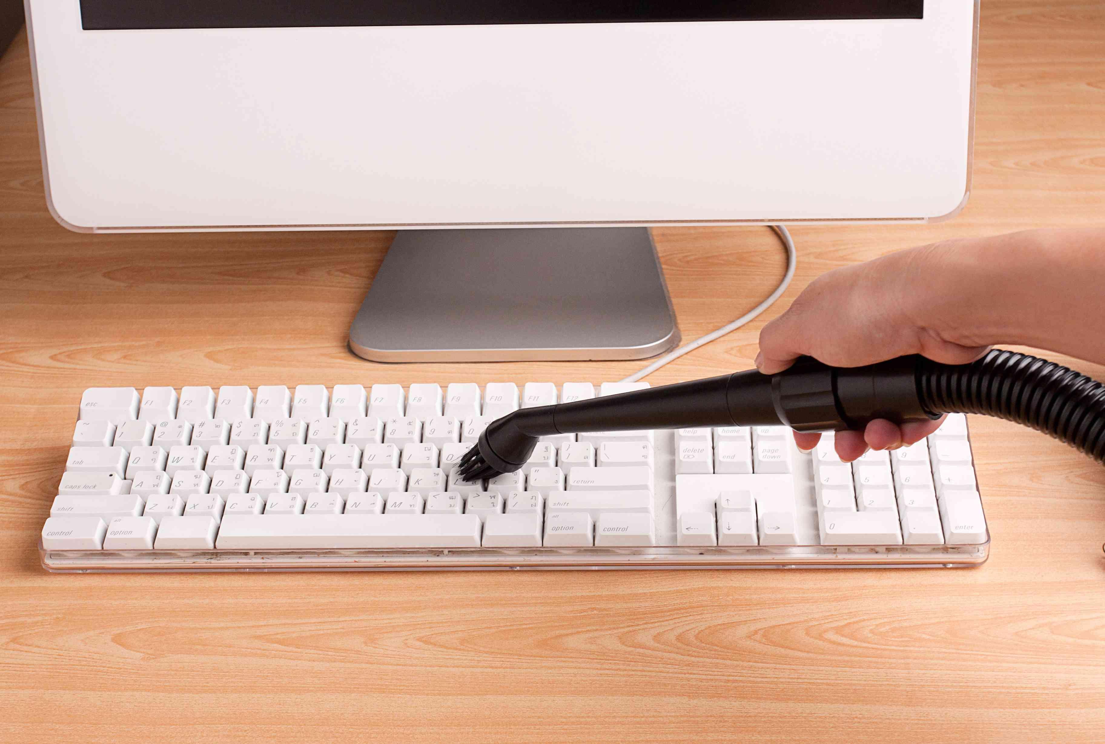 Handheld vacuum used to clean a keyboard
