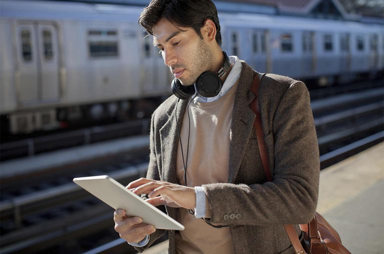 Man using tablet computer at station