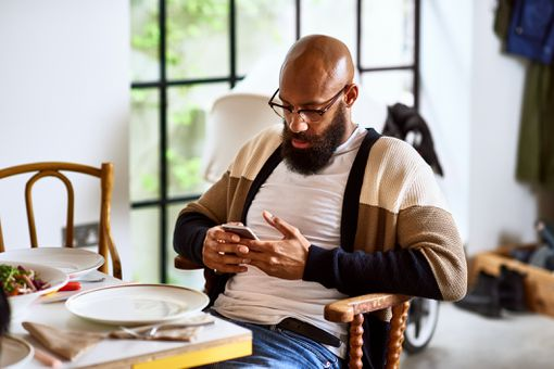 A man sitting in a chair looking at his phone carefully