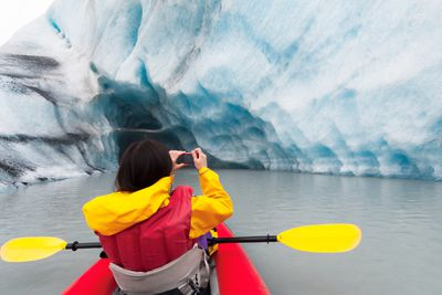 A kayakker taking photos on a point and shoot camera