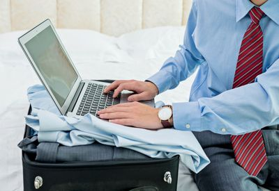 Man working on computer on his luggage in a hotel room