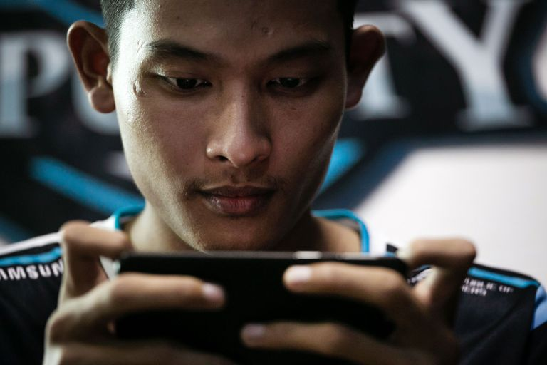 A young man plays a game on his Android phone.