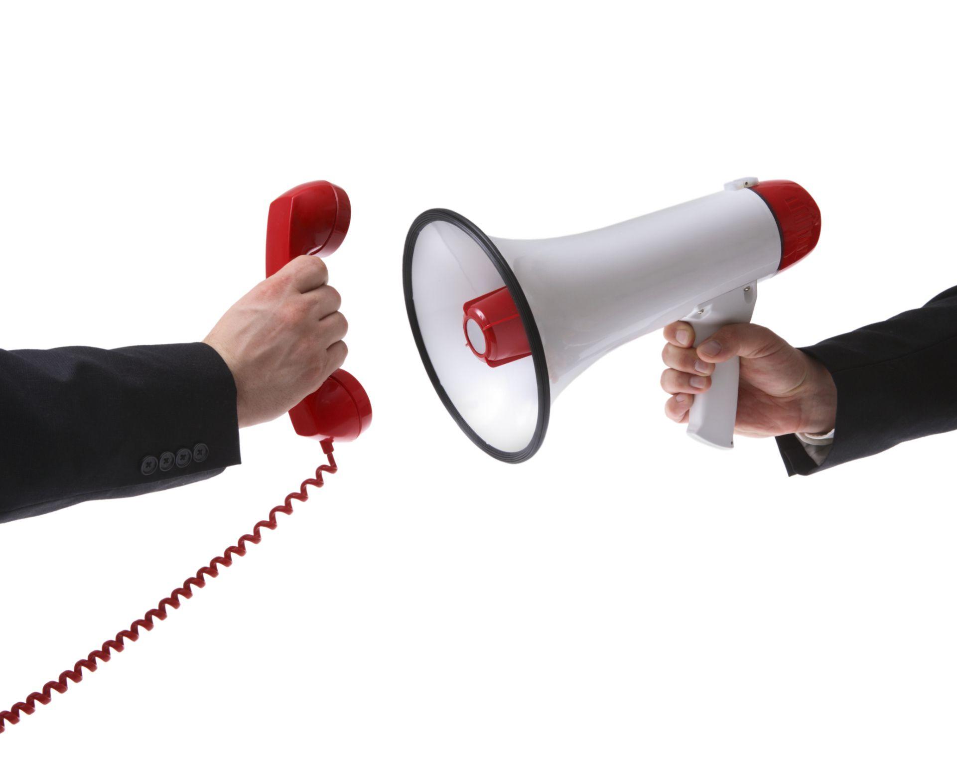 Man holding megaphone up to telephone