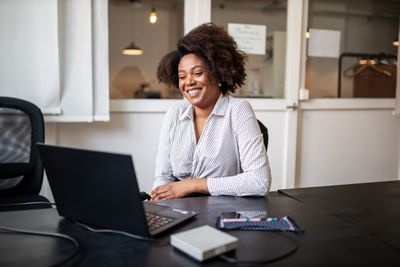 A woman sitting at a desk smiling at her laptop