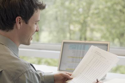 Businessman using a laptop while looking at some printouts