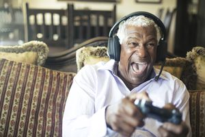 Older man playing video games with a headset on