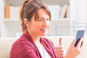 Deaf woman using sign language on the smartphone