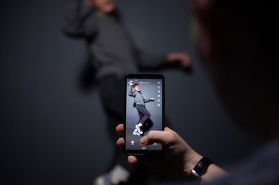 A man filming a video using the TikTok app on a smartphone.