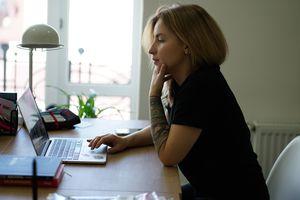 Woman using laptop by window