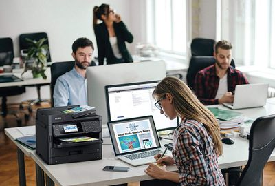 Printer in open office with workers