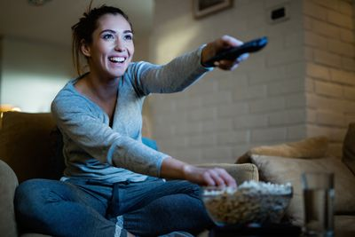 A woman sitting on her sofa smiling holding a TV remote in one hand and dipping her other hand in a bowl of popcorn