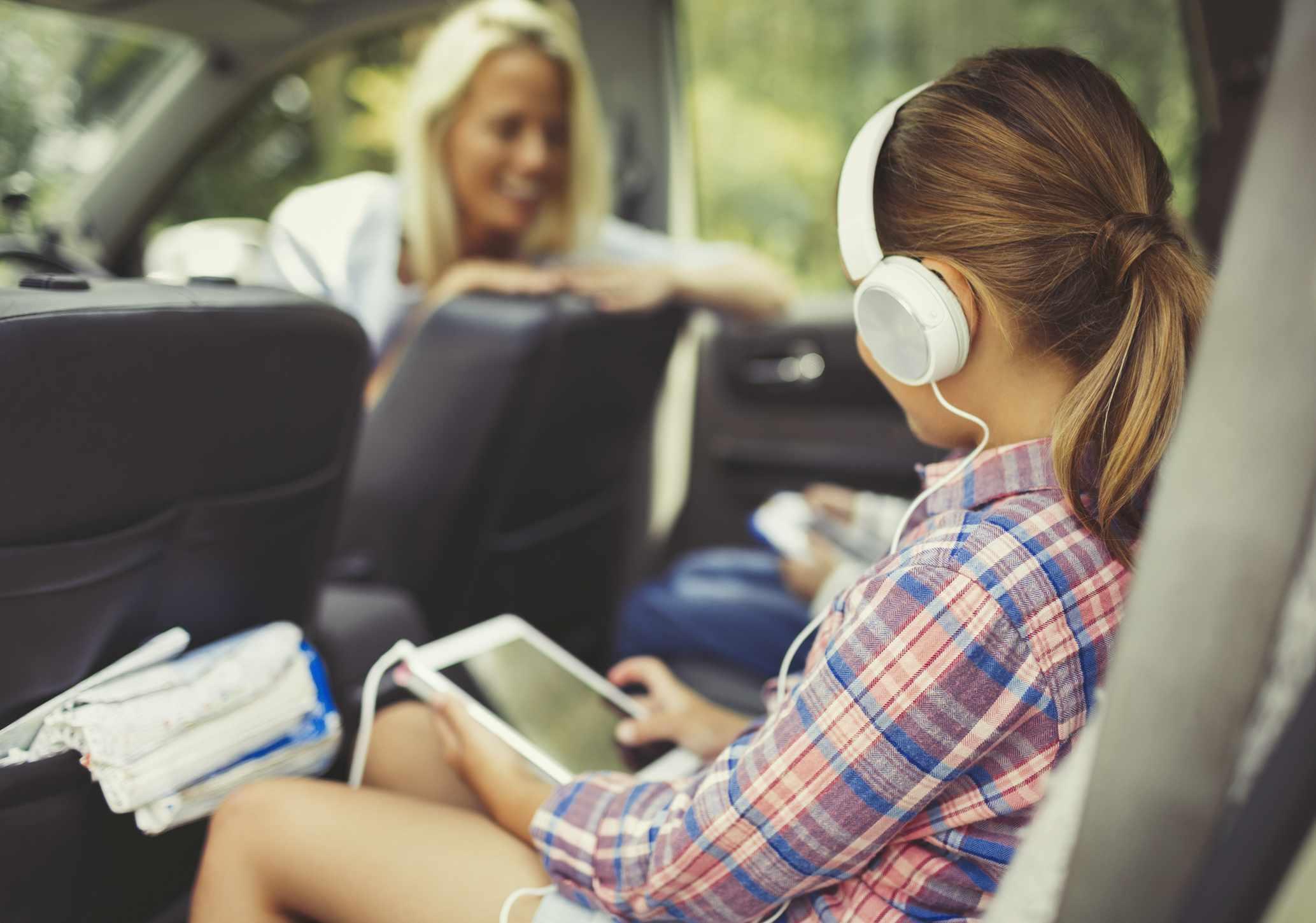 MIddle schooler listening to headphones in a car.
