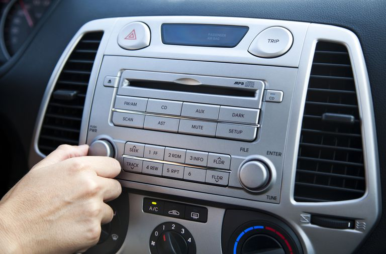 Hand turning a dial on car radio