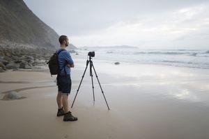 Photographer taking photos on the beach with a tripod