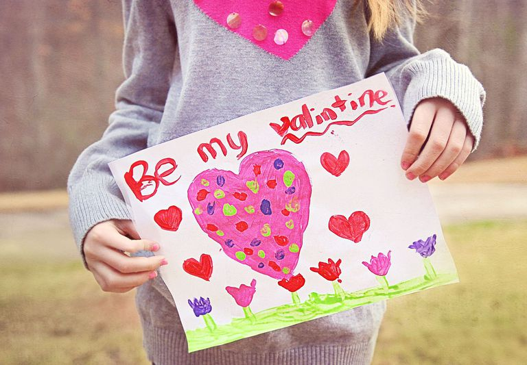 Young girl holding valentine card with pink heart on it that says Be my Valentine