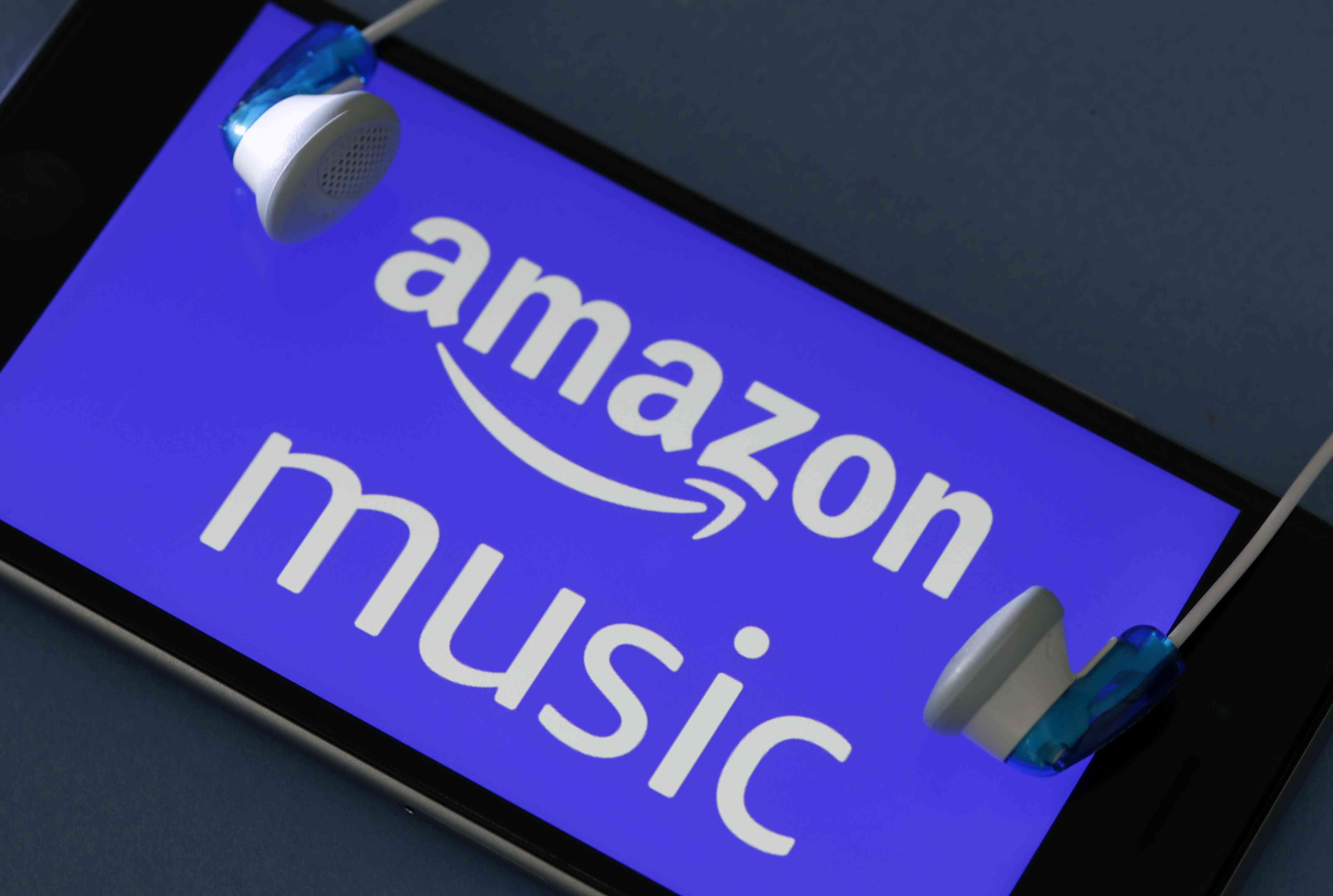 Headphones around smartphone displaying Amazon Music music download service logo