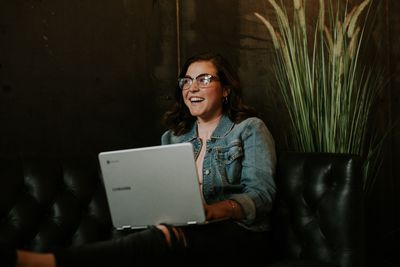 Young woman with laptop on couch laughing