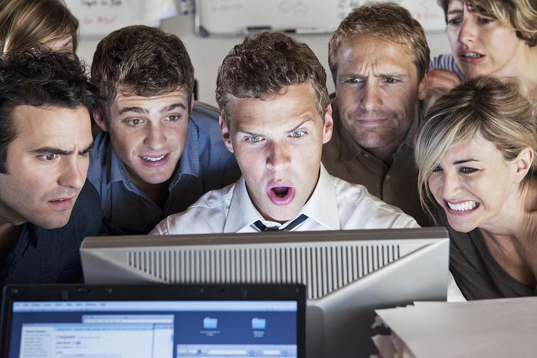 coworkers looking at something shocking on computer