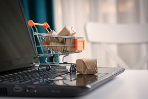A minature shopping cart with small packages on a laptop's keyboard.