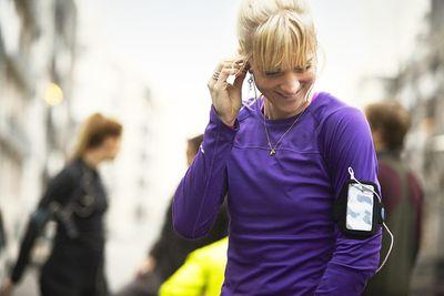 Group of runners preparing in urban environment, athlete plugging in earphones