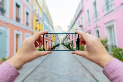 Hands taking a photo of a colorful street with smartphone