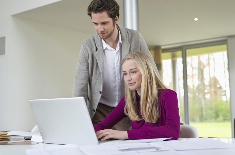 Man looking at a woman working on a laptop