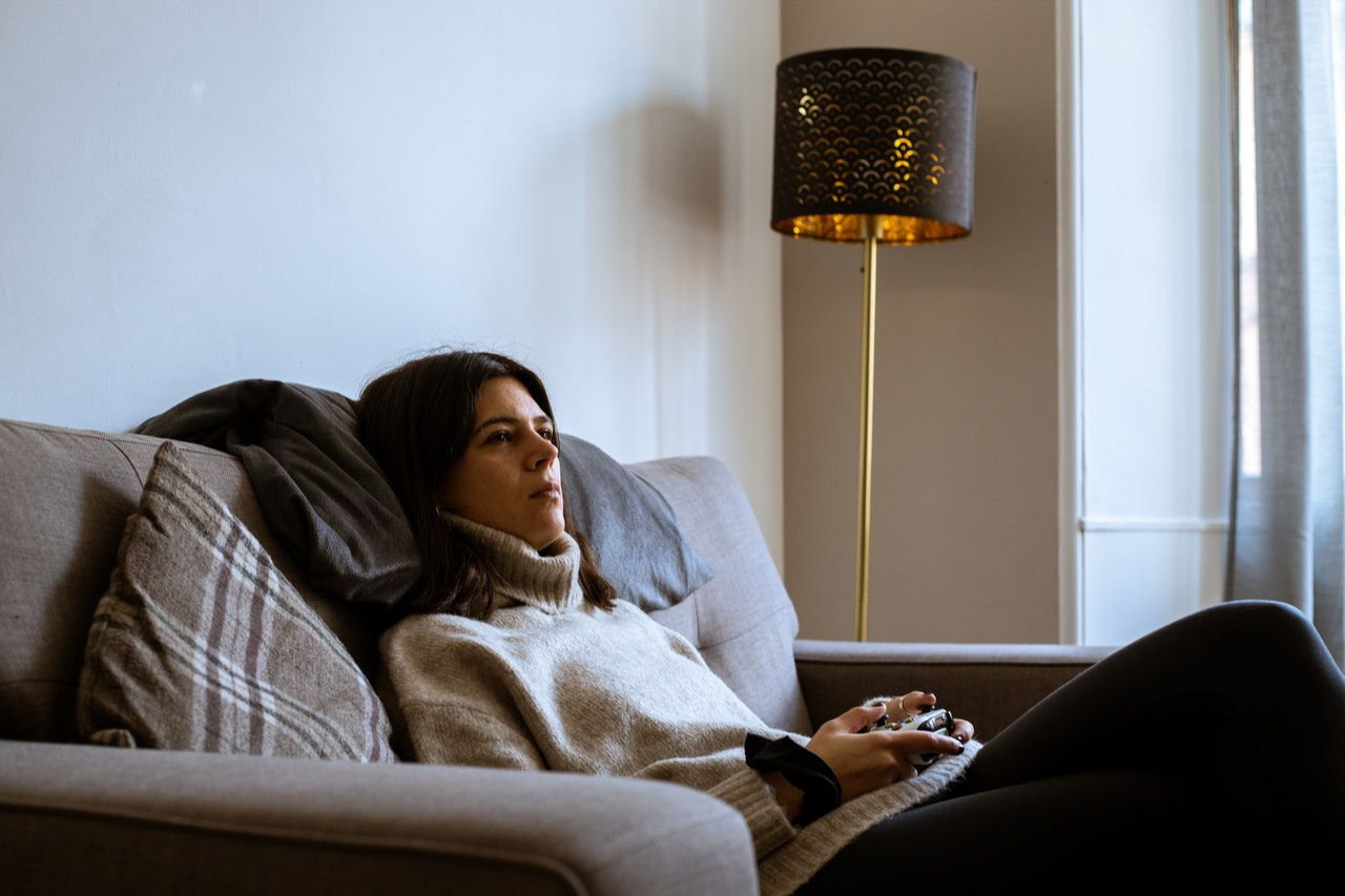 woman in sweater looking on the xbox